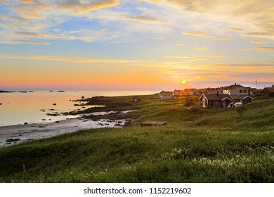 Beautiful summer evening sunset on the coast of the ocean with white sand and houses in Norway Lofoten island, Fredvang, Reine, Ramberg, landscape.