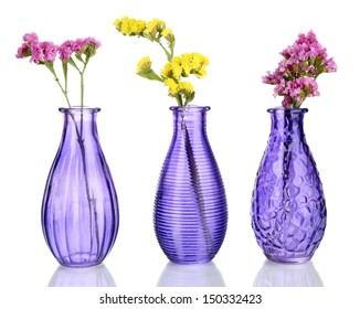 Beautiful summer flowers in vases isolated on white