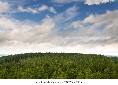 Beautiful summer forest view from Pajndl lookout tower cloudy sky copy space, Tisovsky Mount in Krusne Hory, Bohemia, Czech Republicry