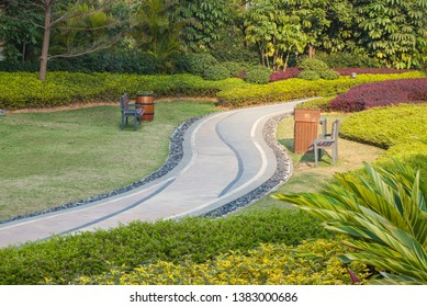 Beautiful summer garden with a walkway winding its way through. The curve walkway with stone tile on green grass field and flowerbed with table and flower pot. China