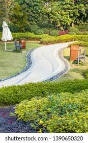 Beautiful summer garden with a walkway winding its way through.Benchs and fower pots by the way. Fuzhou,China