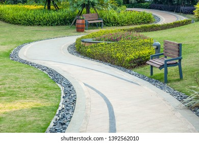Beautiful summer garden with a walkway winding its way through. The curve walkway with stone tile on green grass field and flowerbed with table and flower pot.