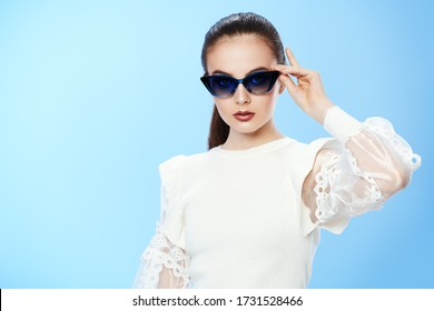 Beautiful summer girl posing in elegant white blouse and sunglasses on a light blue background. Happy smiling girl. Summer fashion and makeup. Optics.