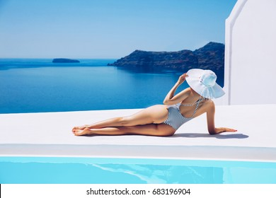 Beautiful summer  girl in white hat and stylish swimsuit on back to the viewer. Summer vacation concept.Santorini,Greece