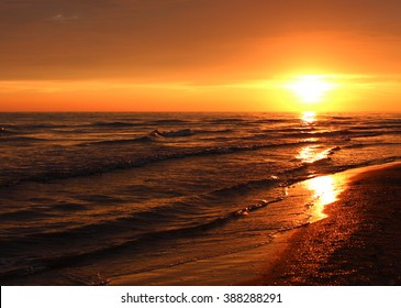Beautiful summer golden sunset above the black sea.with calm waves and reflection of sun on the beach. Sochi, Russia
