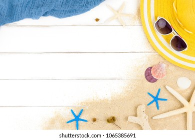 Beautiful summer holiday beach background with some accessories and shells on white wood panel, border design on top view with copy space