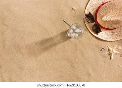 Beautiful summer holiday beach background with straw hat, sunglasses, glass of water and shells on sand background, top view with copy space. Harsh shadows