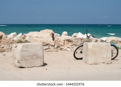 Beautiful summer landscape with bicycle standing behind white stone on the blue seashore, Caesarea, Israel.