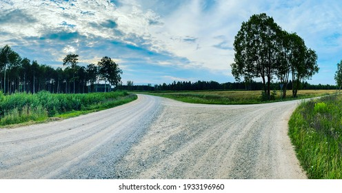 Beautiful summer landscape with a country sand road that divides into an intersection to the right and straight. Tree silhouettes in the blue sky are visible. countryside landscape