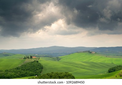 Beautiful summer landscape.  Cypress trees, hills and green fields in Tuscany under the threat of stormy clouds , Italy, Europe