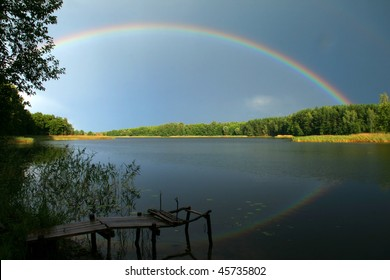 beautiful summer  landscape with rainbow above the lake