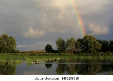 Beautiful summer landscape with a rainbow in the sky and trees by the pond in Russia