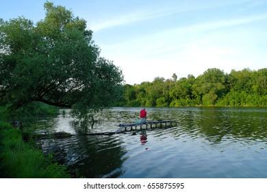Beautiful summer landscape, trees, pond, river.Fisherman.