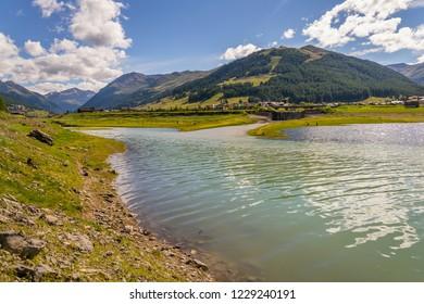 Beautiful summer landscape with Vetta Blesaccia mountain peak and Lake Livigno, Italy, sunny day
