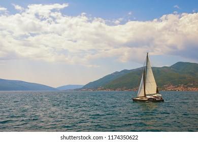 Beautiful summer Mediterranean landscape. Sailboat sails along coast of Kotor Bay . Montenegro .  Travel concept