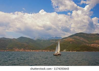 Beautiful summer Mediterranean landscape. Sailboat sails  near shore of Bay of Kotor, Adriatic Sea , Montenegro.  Travel concept