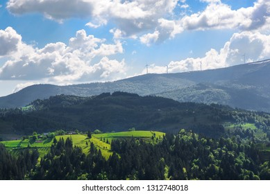 Beautiful summer mountain landscape in Apuseni mountains, Romania. Snow and wind turbines at the top of hills. Concept of green lifestyle, sustainability and energy.