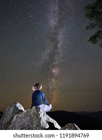 Beautiful summer night in mountains. Back view of female tourist sitting alone on top of huge boulder doing yoga on clear night starry sky with Milky way background. Siddhasana