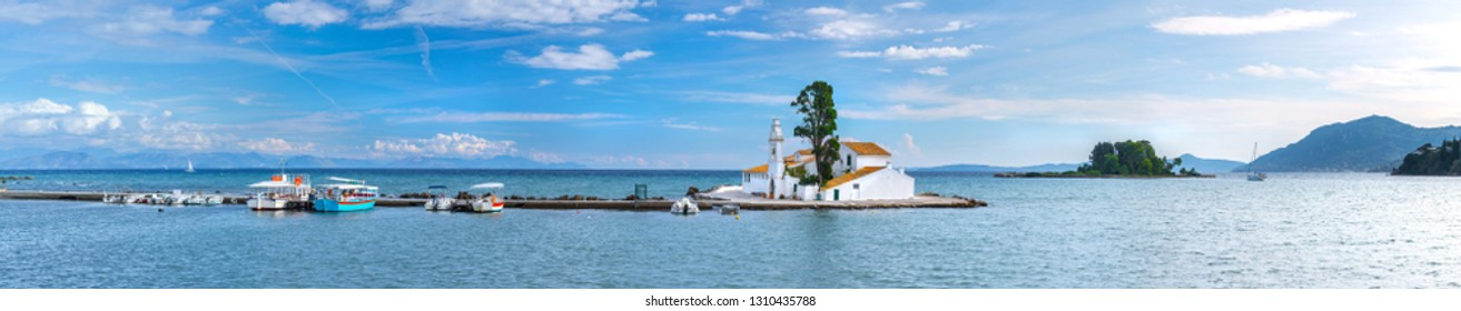 Beautiful summer panoramic landscape of Vlacherna Monastery and island of Pontikonisi or Mouse island in Kerkyra. Green mountain slopes in Mediterranean sea. Corfu. Greece. Europe.