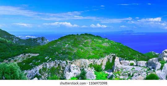 Beautiful summer panoramic seascape. Awesome view of the picturesque green hills and distant islands in the calm warm Mediterranean sea. Outskirts Paleokastrica. Corfu. Ionian archipelago. Greece.