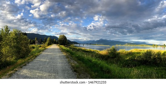 Beautiful summer panoramic view with road, mountains and river. Traboulay PoCo Trail, a 25.3 kilometre route that encircles the community. Port Coquitlam, BC, Canada.