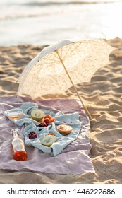Beautiful summer picnic on the beach at sunset in boho style. Organic fresh fruit with natural lemonade on linen blanket with white umbrella. Vegetarian eco idea for weekend picnic.