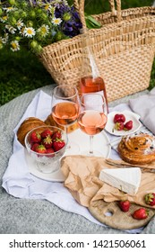 Beautiful summer picnic with strawberries, cheese and rose wine on the lawn in the city park