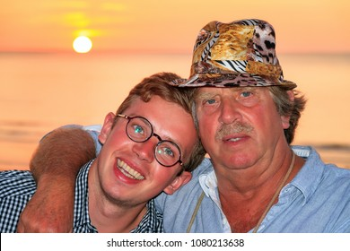 Beautiful summer portrait of a caucasian father and son at sunset on the beach