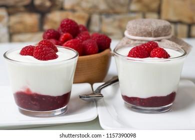 Beautiful summer refreshment. White yogurt with raspberry jam and fresh picked raspberries