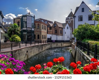 Beautiful summer scene in Kingston upon Thames with canal water among traditional English houses on a sunny day