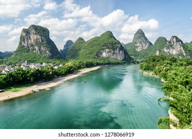 Beautiful summer sunny landscape at Yangshuo County of Guilin, China. Wonderful view of karst mountains and the Li River (Lijiang River) with azure water. Scenic green hills on blue sky background.