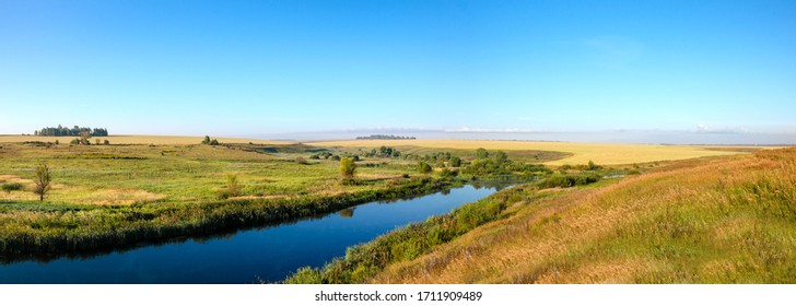 Beautiful summer sunris nature landscape.Breathtaking view of golden wheat fields and waters of calm river.Amazing panoramic view of summer sunrise nature.Tranquil rural scene.River Upa,Tula region.