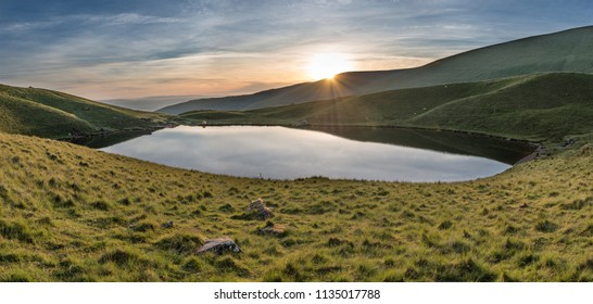 Beautiful Summer sunrise landscape by Llyn Cwm Llwch lake in Brecon Beacons National Park with wild camping