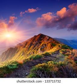 Beautiful summer sunrise in mountains. Path along the ridge leading to summit