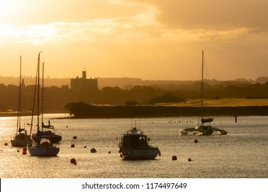 Beautiful summer sunset landscape in Amble town, Northumberland, UK. Yellow and orange sky above water and marina, Warkworth Castle in background.