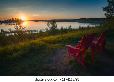 A beautiful summer sunset over a lake with with red chairs