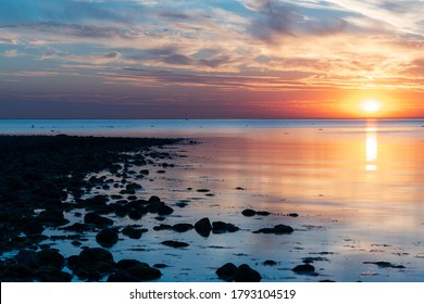 Beautiful summer sunset over stone beach with reflection in the water in Hittarp, Helsingborg, Sweden.