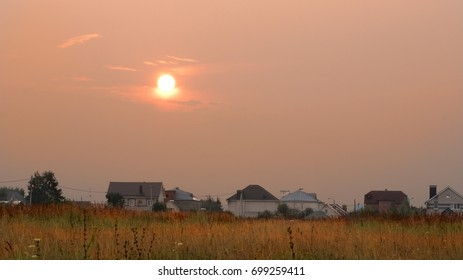 Beautiful summer sunset with red sun over houses.