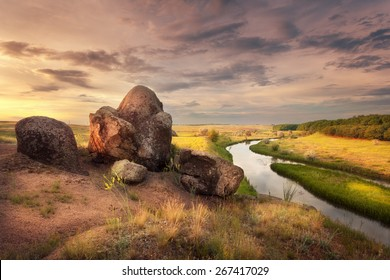 Beautiful summer sunset at the river with orange sky, clouds, rocks, yellow grass, flowers and water with reflection. Ukraine