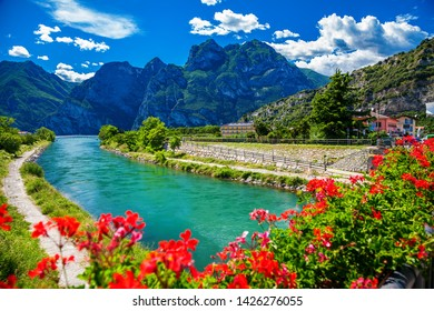 beautiful summer view of the Sarca river through red flowers in a small town Torbole, lake Garda, Italy