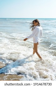 Beautiful summer woman walking in sea water with waves at hot sunny day, wearing flowy white shirt. Freedom and paradise concept