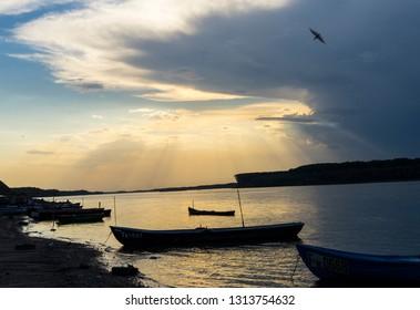 Beautiful sun beams over a river and fishing boats