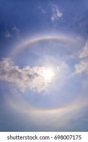 beautiful sun halo with circular rainbow around sun behind blue sky and clouds. fantastic natural phenomenon