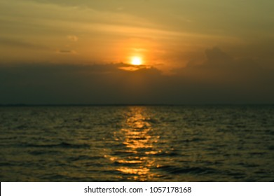Beautiful sun rise at the beach with golden light in the sky and  glitter bokeh on sea surface.The image is suitable as a background in various occasion such as romantic,sad,hope.