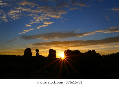 A beautiful sun rises over the Balancing Rock formation in Arches National Park, Utah.