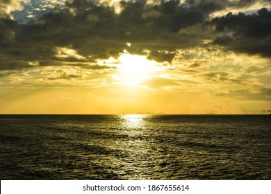 Beautiful sunbeam from sunset under overcast clouds that over calm sea at tropical island. Sunlight reflection. Scenic seascape in the evening at beachfront in Lipa Noi beach, Samui island, Thailand.