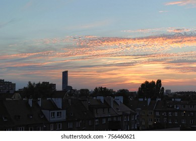 Beautiful sundawn or sunset sky above houses. Beautiful clouds and colors. Great urban architecture cityscape. Old buildings and new skyscrapers interspersed with trees. Wonderful urban landscape.
