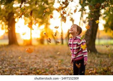 Beautiful sundown scene as girl child enjoys herself in an autumn park