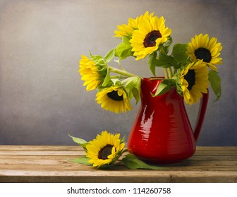 Beautiful sunflower bouquet in red jug on wooden tabletop.