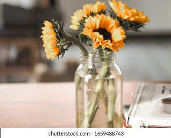 Beautiful Sunflower Flowers In A glass Vase .  Sunflower Table Decorations .   Home Decoration Flower Glass Vase with Sunflowers on woodle background .